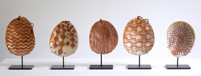 Five carved pearl shells with red ochre image