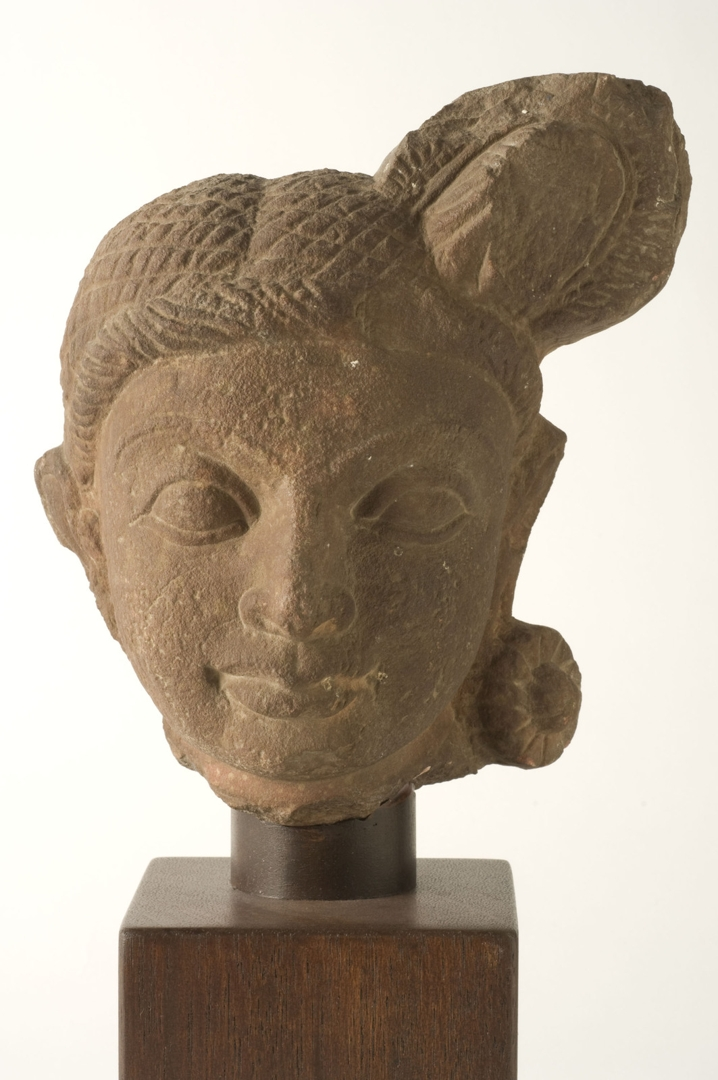 Sandstone head of female devi with elaborate coiffure and earring image