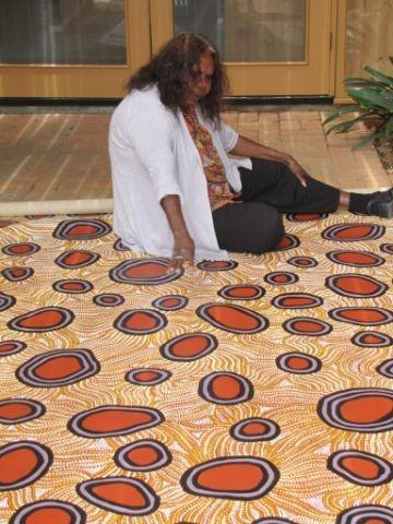 Maureen Hudson Nampitjinpa with her painting Pinta Pinta Waterholes image