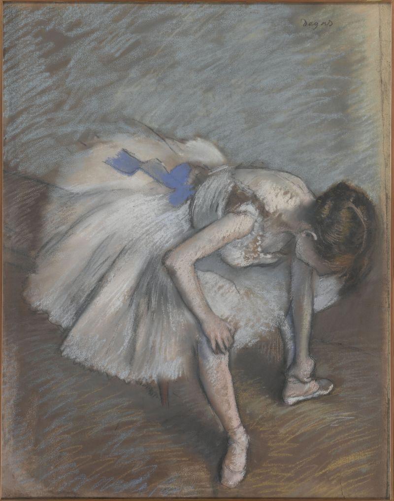 Seated dancer leaning forward, massaging her left foot image