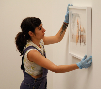 "Kymia Nawabi, winner of Work of Art: The Next Great Artist, season two, installing a work in the episode ""The Big Show."" image"